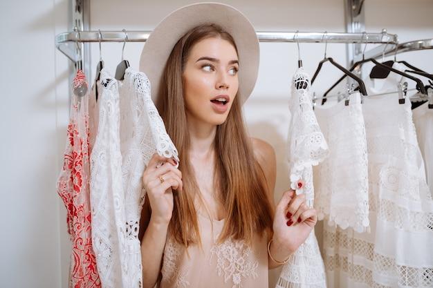 Удивленная любопытная молодая женщина в шляпе стоит в магазине одежды и смотрит в сторону