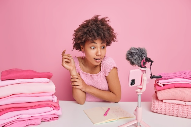 Surprised curly afro american woman focused at smartphone camera records live stream broadcasting video gives useful tips how to care about clothes sits at table with piles of folded laundry