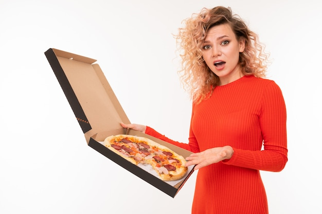 Surprised curly blond girl in a red dress holds a box of pizza on white