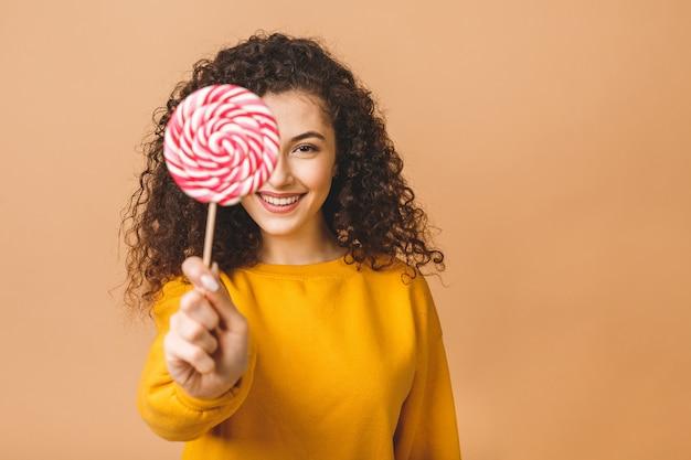 ロリポップを食べて驚いた巻き毛の少女。ベージュ色の背景に分離されたピンクの甘いカラフルなロリポップキャンデーを保持している美容モデル女性。
