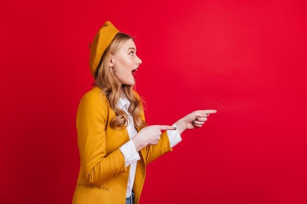 指で指しているベレー帽の驚いた巻き毛の女の子。赤い壁に隔離されたうれしそうなブロンドの女性。