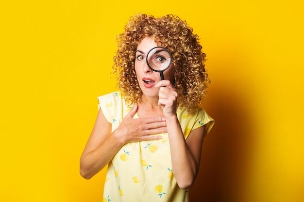 Удивленная кудрявая девушка смотрит через увеличительное стекло на желтой поверхности