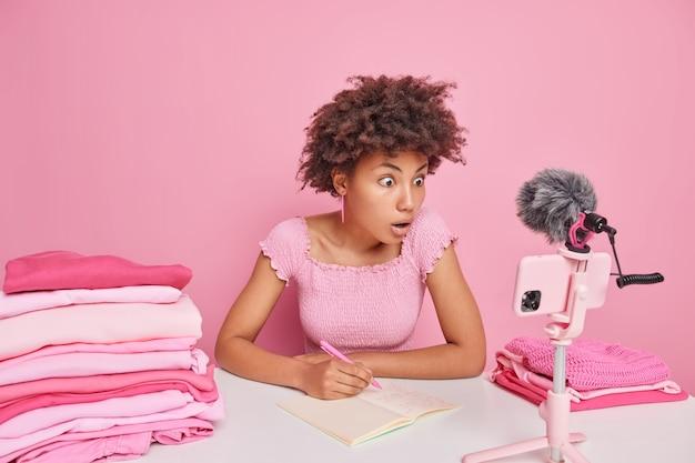 驚いた縮れ毛のアフリカ系アメリカ人女性が、きちんと折りたたまれた洗濯物の山に囲まれたテーブルに座って、スマートフォンのカメラに焦点を当てたノートにメモを書きます国内のルーチンについてのビデオブログを作成します