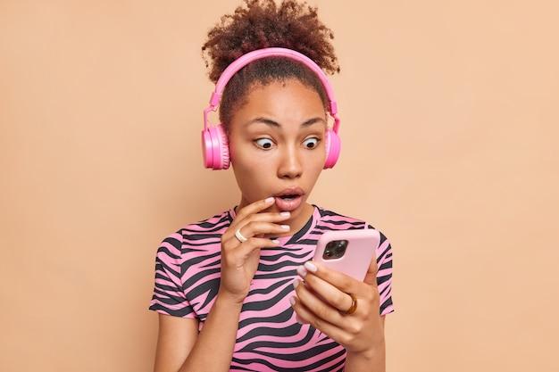 驚いた縮れ毛の民族女性がスマートフォンのディスプレイの更新を凝視プレイリストはステレオワイヤレスヘッドフォンを着用ベージュの壁に分離されたストライプのtシャツは衝撃的なニュースに反応します