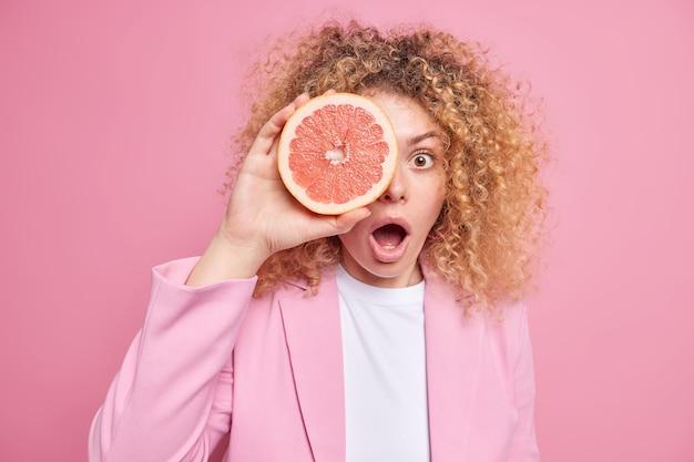 驚いた巻き毛のヨーロッパの女性は、グレープフルーツのスライスで目を覆い、ピンクの壁に隔離されたスタイリッシュな服を着て口を開けたままにします。夏のリフレッシュメント。柑橘系の果物のコンセプト。