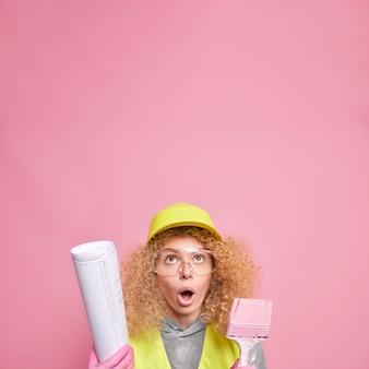 ショックを受けた表情で上に焦点を当てた驚いた縮れ毛の女性建設労働者は、ピンクの壁に隔離された建築プロジェクトの青写真とペイントブラシの作品を保持しています