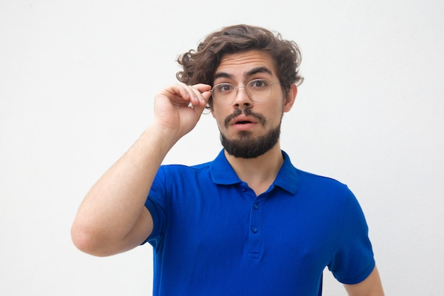 Surprised curly haired guy putting on glasses