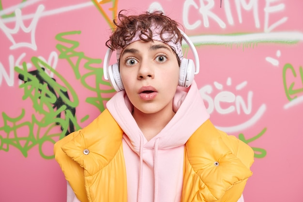 Surprised curly haired hipster guy looks with wonder at camera listens music via wireless headphones dressed in sweatshirt and vest poses against colorful graffiti wall