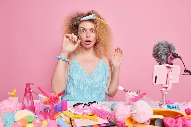 놀란 곱슬머리 여성이 화장에 대한 짧은 리뷰를 작성하여 속눈썹 뷰러를 사용하는 방법을 알려줍니다. 온라인 라이브 스트리밍 비디오는 분홍색에 반대하여 테이블에 앉아 있습니다.