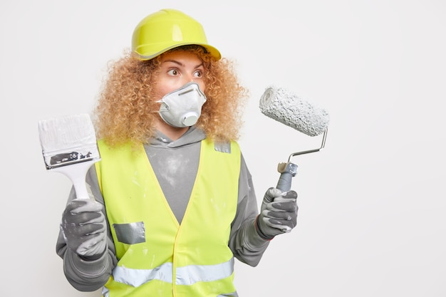 Surprised curly haired woman builder wears construction helmet safety clothe protective mask holds building equipment for house refurbishment stands against white wall copy space for inscription