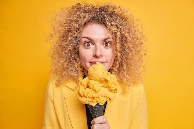 Surprised curly haired woman eats delicious ice cream doesnt care about calories looks with impressed happy expression  isolated over yellow wall. female has gelato for dessert