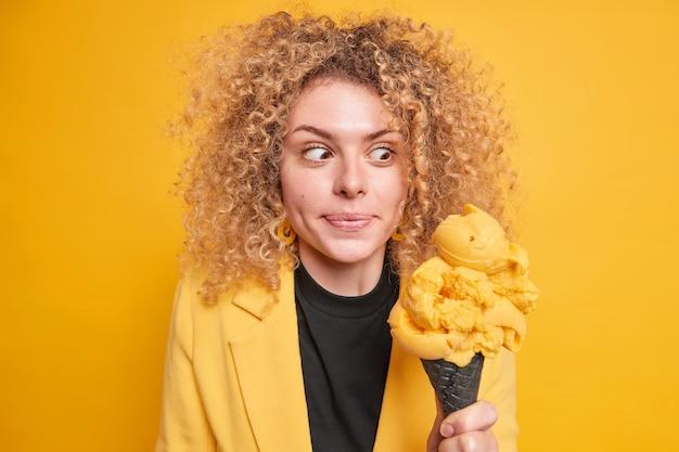 놀란 곱슬 머리 여자는 식욕을 돋우는 아이스크림을보고 세련된 옷을 입은 고 칼로리 디저트를 먹고 싶은 유혹을 느낀다.