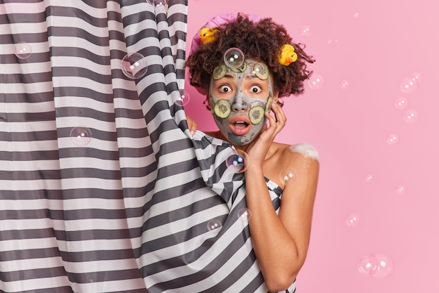 놀란 곱슬 머리 여자가 화장실에서 샤워를하고 분홍색 벽 위에 고립 된 영양 피부를 위해 클레이 마스크와 오이 조각을 적용하여 커튼 뒤에 알몸을 숨 깁니다.