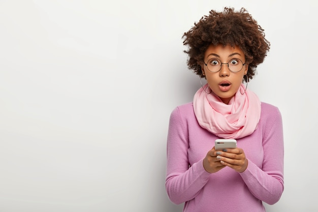 Surprised curly haired woman wears glasses, holds mobile phone, gets message, looks with shocked expression, wears round eyewear