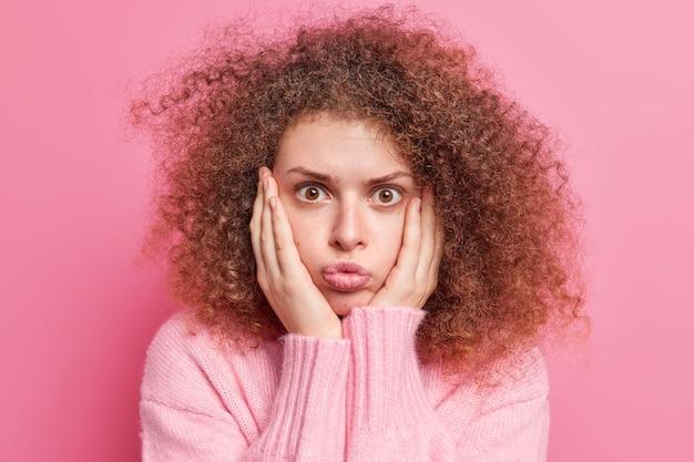 Удивленная кудрявая молодая европейка держит руки на щеках, потрясенно смотрит, надувает губы, замечает что-то невероятно одетое, небрежно изолированное над розовой стеной. omg концепция