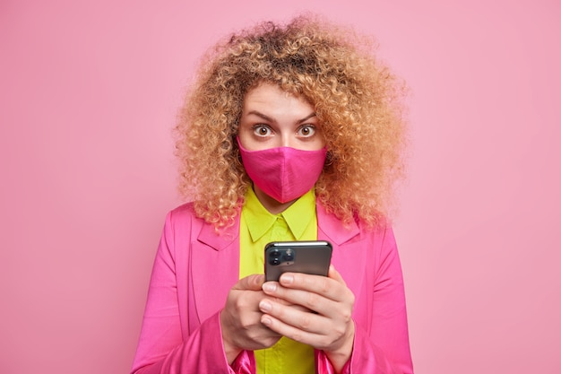 Surprised curly haired young woman covers mouth to be safe holds mobile phone dressed in formal clothes sends text messages isolated over pink wall. social distancing during quarantine
