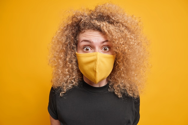 Surprised curly haired young woman stares  wears yellow protective mask encourages stay safe during coronavirus outbreak dressed in black t shirt poses indoor. social distancing concept