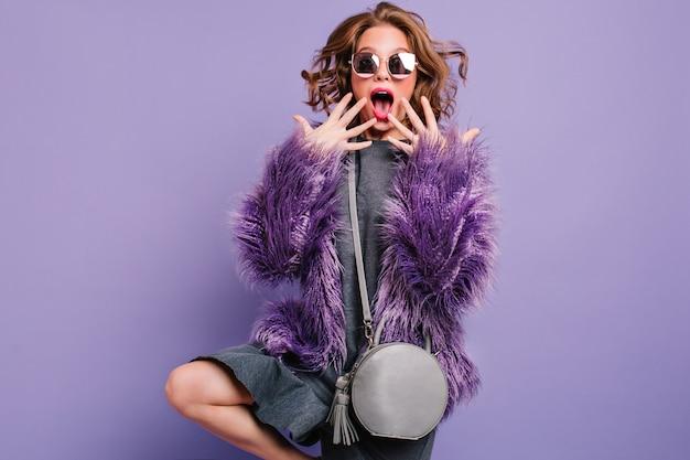 Удивленная кудрявая женщина с серым кошельком, стоя на одной ноге в студии