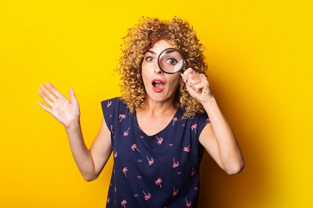 Удивленная кудрявая молодая женщина смотрит в камеру через увеличительное стекло на желтой поверхности