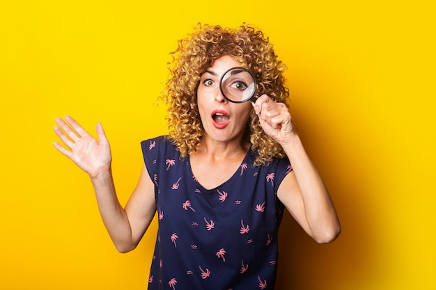 Surprised curly young woman looks at the camera through a magnifying glass on a yellow surface