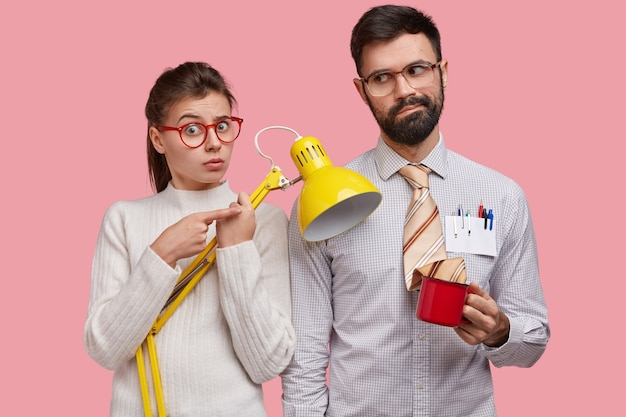Surprised cute female student carries lamp, upset indecisive unshaven man drinks tea, wears big spectacles and formalwear