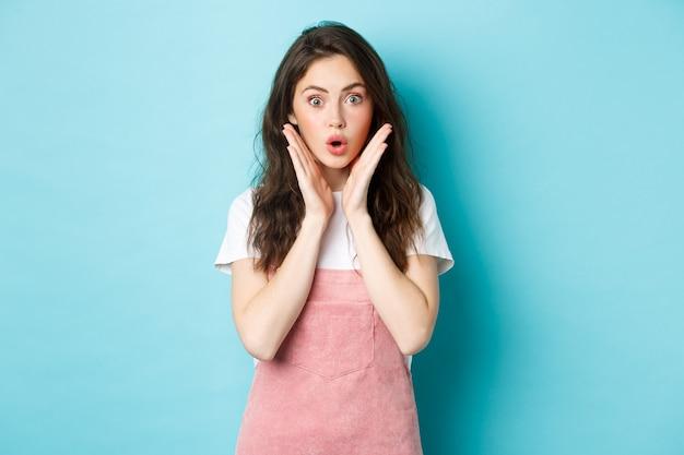 Удивленная милая девушка, задыхаясь от удивления, говорит «вау» и с удивлением смотрит в камеру, слышит интересные новости, просматривает промо-предложение, стоит на синем фоне