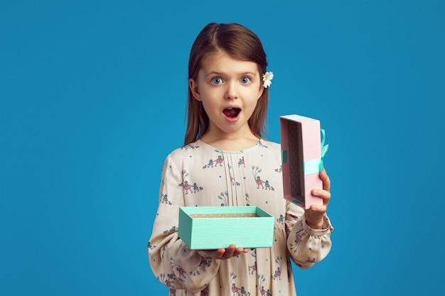 Удивленная милая девушка держит открытую подарочную коробку над синей стеной