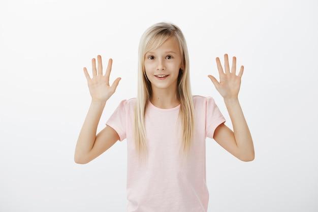 驚いたかわいい女の子は手を上げると笑顔