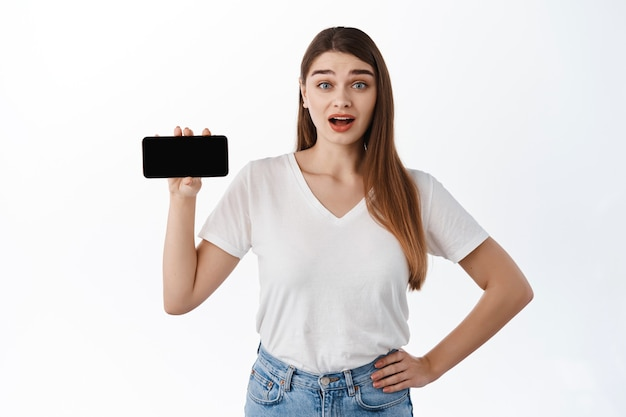 驚いたかわいい女の子はスマートフォンで水平画面を表示し、驚いて眉を上げ、リンク、ウェブサイトまたはアプリケーションを共有し、オンラインで素晴らしいコンテンツ、インターネットで何かを見つけました、白い壁
