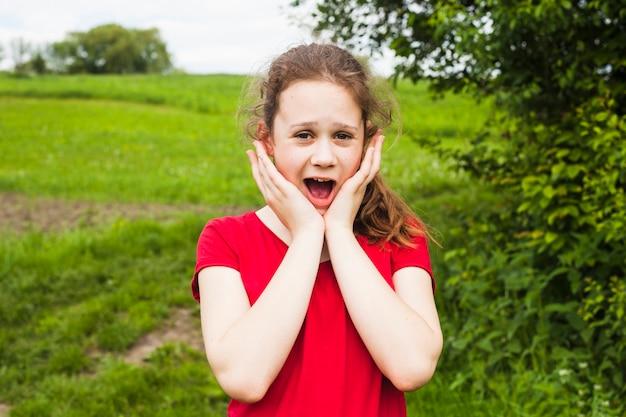 Surprised cute girl standing in beautiful park