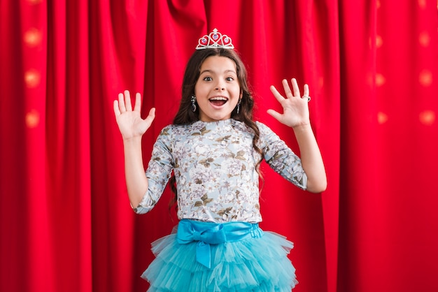 Surprised cute girl wearing crown standing in front of red curtain
