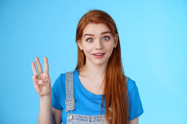 놀란 귀여운 빨간 머리 백인 소녀 쇼 3번, 3번째, 손가락 세기, 눈썹 올리기, 기묘하게 웃고, 파란색 배경 장난기 넘치는 부드러운 표정