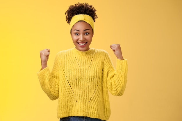 Surprised cute tender african-american girl cannot believe win prize lottery clench fists triumphing smiling broadly widen eyes impressed astonished celebrating success, victory yellow background.