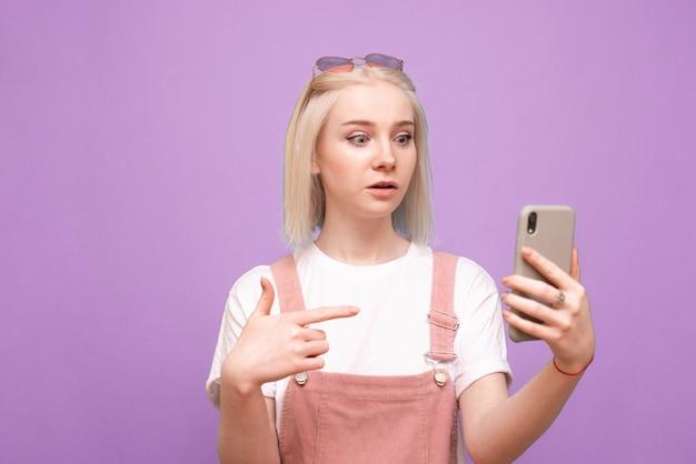 놀란 귀여운 여자는 그녀의 손에 스마트 폰에 손가락을 보여주고 화면을 쳐다 본다.