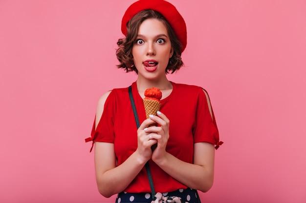 アイスクリームを食べて驚いた暗い目の女の子。かなりスタイリッシュなフランス人女性のポーズ。