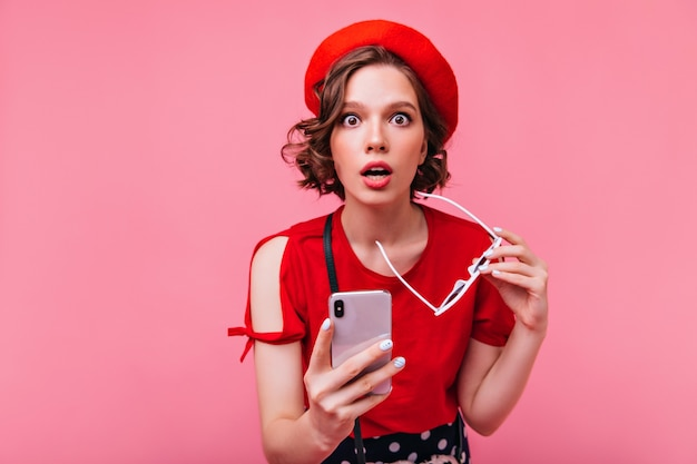 Удивленная темноволосая девушка позирует с телефоном. хорошо одетая барышня в берете выражает изумление.
