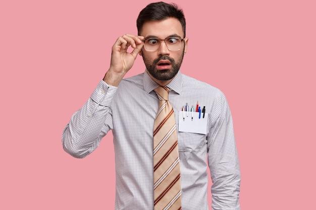 Удивленный темноволосый молодой человек скрещивает глаза, держит руку на оправе очков, одетый в строгую одежду
