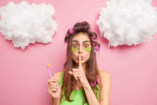 Surprised dark haired young woman makes hush gesture tells secret of beauty brushes teeth undergoes skin care procedures applies hair rollers poses against pink wall
