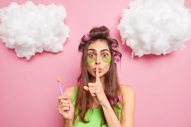 驚いた黒髪の若い女性が静けさのジェスチャーをし、美容ブラシの秘密を告げる歯はスキンケア手順を受け、ピンクの壁にヘアローラーポーズを適用
