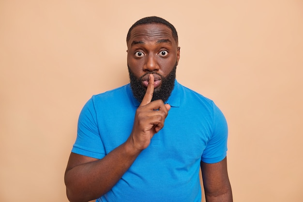 Surprised dark skined man with thick beard presses index finger to lips makes silence gesture asks to be quiet and not to spread rumors wears casual blue t shirt isolated over beige wall