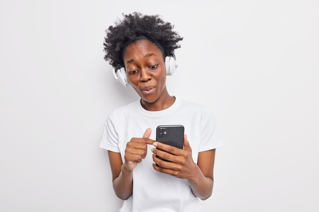 Surprised dark skinned curly female model points at smartphone display reads great news has wondered expression