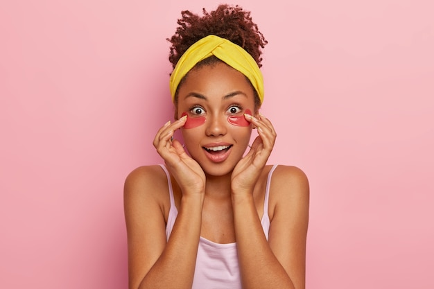 눈 아래 콜라겐 패치가있는 놀란 짙은 피부의 곱슬 젊은 여성은 인상적으로 보이며 미용 제품의 놀라운 활력 효과를 궁금해하며 노란색 머리띠와 티셔츠를 입습니다.