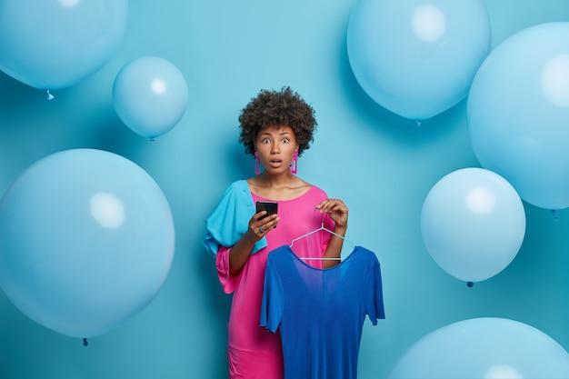 Sorpresa donna dalla pelle scura sceglie il vestito, tiene il vestito blu sui ganci, utilizza lo smartphone e fa acquisti online nella boutique di moda, si prepara per un appuntamento o una festa, isolato sul muro blu