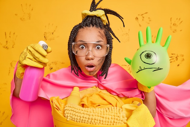 Surprised dark skinned female housekeeper stares at camera holds detergent and inflated balloon wears big transparent glasses cape pretends being superhero ready for cleaning or removing dirt