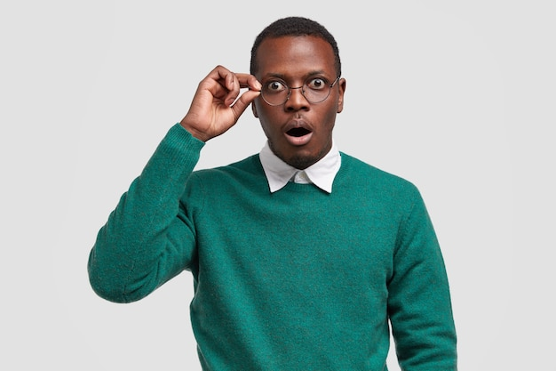 Surprised dark skinned male teacher keeps hand on rim of glasses, wears elegant white shirt and green sweater