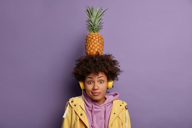 Sorpresa ragazza millenaria dalla pelle scura porta ananas maturo sulla testa, ascolta musica, indossa le cuffie sulle orecchie, trascorre il tempo libero ascoltando la canzone preferita vestita casualmente in posa al coperto. donna con frutta