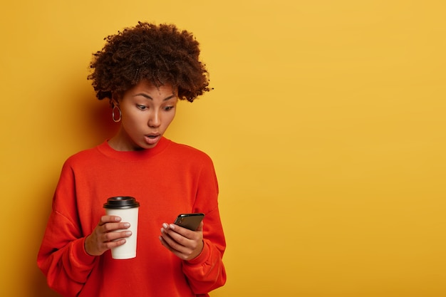 Surprised dark skinned woman, shocked to see new post, connected to wireless internet, reads astonishing news in internet