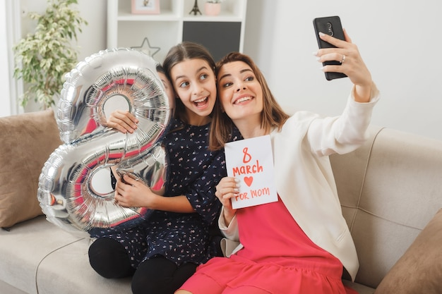 Figlia e madre sorprese con palloncino numero otto e cartolina il giorno della donna felice seduta sul divano si fanno un selfie in soggiorno
