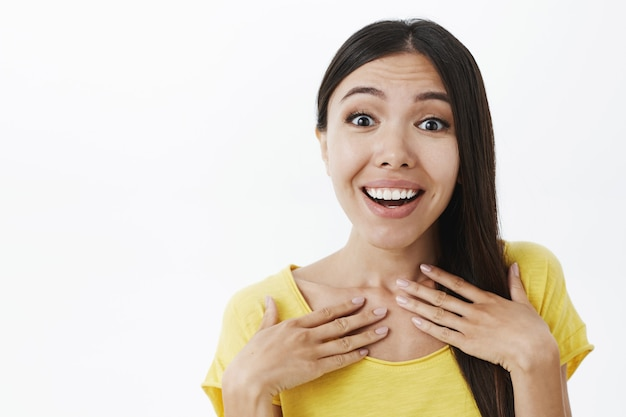 Surprised delighted attractive woman with lond dark hair holding palms on chest gasping