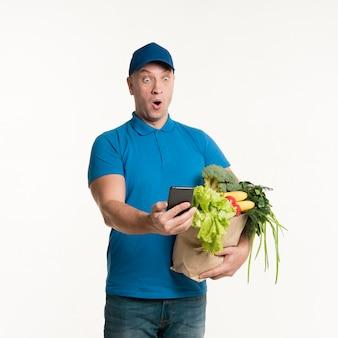 Удивленный доставщик смотрит на телефон, держа продуктовый мешок